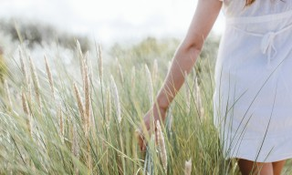 Woman walking through grass on sand dune